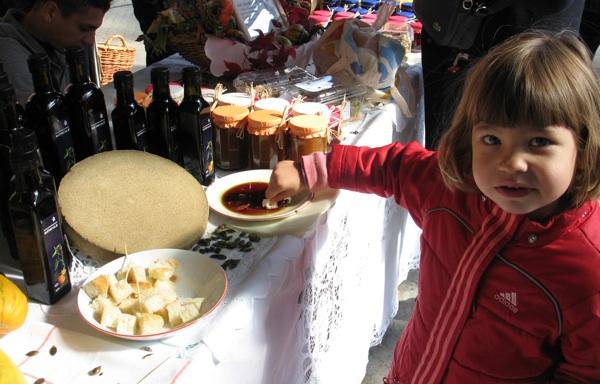 Promocija bučina ulja od malih nogu: unučica Marice Svetlečić, tajnice udruge proizvođača ulja Hrvatske, kuša bakino ulje na štandu na Bučijadi (Snimila Božica Brkan / Acumen)